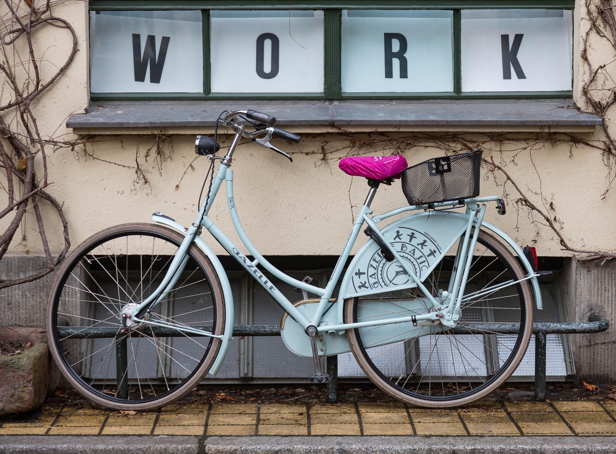 """Parkerad cykel under fönster med texten """"Work""""."""